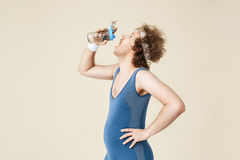 Side shot of thursty man drinking water from glass bottle. Retro sport clothing. Sport concept royalty free stock photography