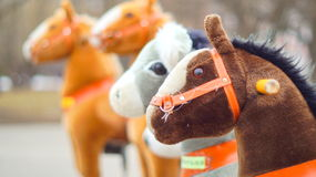 Side-show of rocking horses in park Royalty Free Stock Photos