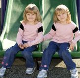 Side By Side. Twins side by side on a park slide Royalty Free Stock Photos