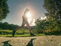 Side silhouette of active man exercising and running on the road stock photography