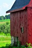 Side of small New England Style red barn in Hoillis New Hampshire. Single window looks our on an orchard on a hillside behind the barn. Location is Hillborough royalty free stock images