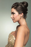 Side of a smiling elegant woman in golden dress. Looking away from the camera Stock Photography