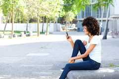 Side of smiling woman holding smart phone in urban park Royalty Free Stock Photography