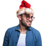 Side  smilling man wearing santa hat looking away. Side view of a smilling young man wearing santa hat looking away from the camera Stock Photography