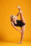 Side splits dance pose by woman against yellow Royalty Free Stock Images