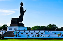 Side of the standing buddha image on beautiful blue sky. Royalty Free Stock Photography