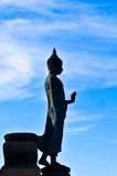 Side of the standing buddha image on beautiful blue sky. Royalty Free Stock Photo