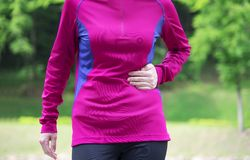 Side stitch. Woman runner side cramps after running. Jogging woman with stomach side pain after jogging work out stock photography