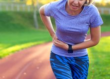 Side stitch - woman runner side cramps after running. Jogging woman with stomach side pain after jogging work out. Female athlete stock images