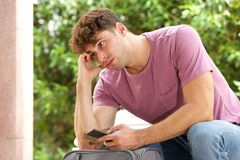 Side of stressed man sitting on park bench with suitcase and cellphone Royalty Free Stock Photos