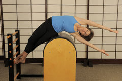 Side Stretch on Pilates Barrel Stock Image