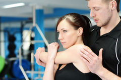 Side stretching with personal trainer royalty free stock photography