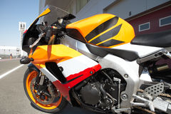 Side of a superbike. Orange superbike next to the racetrack stock photo