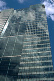 Side of tall glass office building. Against cloudy blue sky stock photo