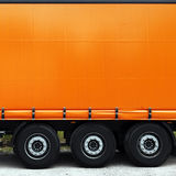 Side of truck or lorry. Blank orange side of semi-trailer truck or lorry with copy space stock photo