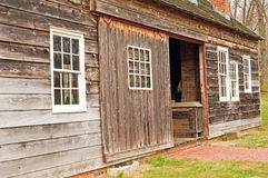 Side of unpainted barn. A view of the side of an old, antique, weather-beaten barn or shed with a sliding doorway Royalty Free Stock Images