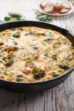 Side vertical view of baked egg fritatta. Baked egg frittata with spinach, cheese, broccoli, red potatoes, bacon, milk, and spinach side vertical view Stock Photos