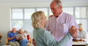Side view of active Caucasian senior couple dancing at nursing home 4k stock video