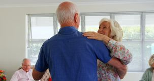 Side view of active Caucasian senior couple dancing at nursing home 4k stock footage