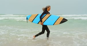 Side view of active senior African American female surfer running towards sea on the beach 4k stock video footage