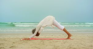 Side view of active senior African American woman doing yoga on exercise mat at the beach 4k stock video footage