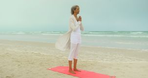Side view of active senior African American woman doing yoga on exercise mat at the beach 4k. Side view of active senior African American woman doing yoga on stock video footage
