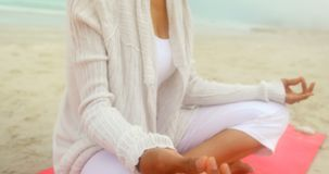 Side view of active senior African American woman doing yoga on exercise mat at the beach 4k. Side view of active senior African American woman doing yoga on stock footage