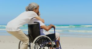 Side view of active senior African American woman embracing disabled senior man on the beach 4k. Side view of active senior African American woman embracing stock footage