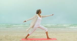 Side view of active senior African American woman exercising on exercise mat at the beach 4k. Side view of active senior African American woman exercising on stock footage