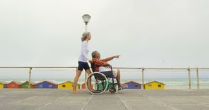 Side view of active senior African American woman pushing disabled man in wheelchair on promenade 4k. Side view of active senior African American woman pushing stock video footage