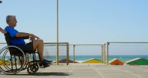 Side view of active senior Caucasian woman pushing senior man on wheelchair at beach 4k. Side view of active senior Caucasian woman pushing senior man on stock footage