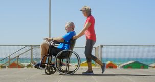 Side view of active senior Caucasian woman pushing senior man on wheelchair at beach 4k. Side view of active senior Caucasian woman pushing senior man on stock video