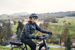A side view of senior woman with electrobike cycling outdoors in countryside. stock images