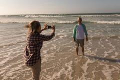 Senior woman clicking photo of senior man on the beach. Side view of active senior women clicking photo of senior men on the beach royalty free stock photos