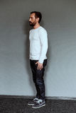 Side view of an actor standing on grey backdrop. Side view of man in full length posing for casting Royalty Free Stock Photography