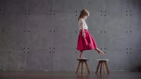 Little girl walking on small chairs, slow motion. Side view of an adorable little girl wearing a pink skirt walking on small wooden chairs in a gray wall room stock video