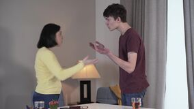 Side view of adult Caucasian woman and teenage boy arguing and gesturing emotionally indoors. Son and mother quarrelling