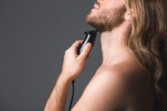 Neat young man using shaver. Side view of adult guy shaving his beard with electric razor. Isolated on grey background Stock Image