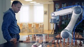 Side view of an adult man playing chess with a robotized arm stock video footage