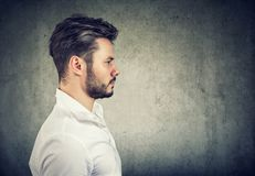 Side view of a modern man in white shirt looking serious on gray background. Side view of adult modern man in white shirt looking serious on gray background royalty free stock images