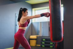 Slim female punching boxing bag stock image