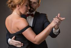 Voluptuous lovers dancing with intimacy. Side view of affectionate couple expressing their passion in dance. Woman is wearing elegant black dress while men is in Royalty Free Stock Photography