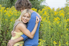 Side view of affectionate couple hugging in field Royalty Free Stock Photo