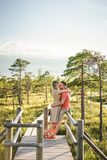 side view of affectionate couple hugging on wooden bridge with green plants and blue sky stock image
