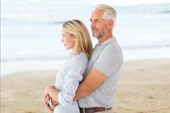 Side view of affectionate senior couple standing at beach. Digital composite of Side view of affectionate senior couple standing at beach Stock Photo