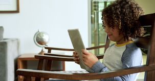 Side view of African american boy playing game on digital tablet on chair in lobby at hospital 4k stock footage