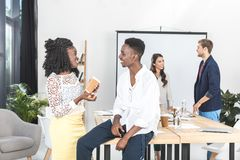 Side view of african american businesspeople talking together with multiethnic coworkers behind. In office royalty free stock photos