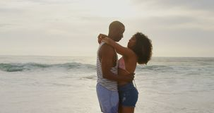 Side view of African American couple dancing together on the beach 4k. Side view of African American couple dancing together on the beach. They are spending time stock video