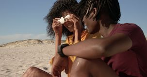 Side view of African american couple playing with seashell on the beach 4k. Side view of African american couple playing with seashell on the beach. They are stock video footage
