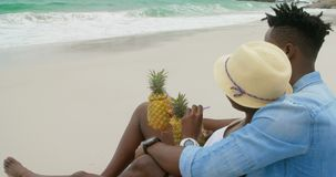 Side view of African american couple relaxing on the beach 4k. Side view of African american couple relaxing on the beach. They are drinking pineapple juice 4k stock video